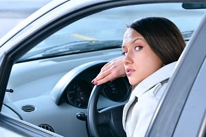 beautiful sensual woman put her head on steering wheel and looki