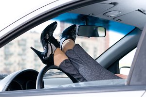 slim female legs are lying on steering wheel