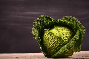 Close up of organic savoy cabbage on the wooden background