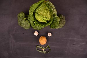 funny face from vegetables on black ground