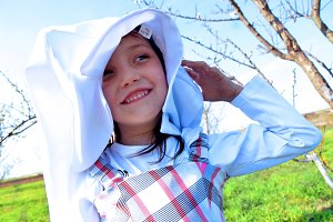 Sweet little girl outdoors with coat on her head