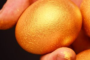 Man holding in hands a golden eggs - investment concept