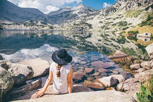 Girl looking out to a mountain lake