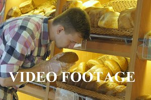 Young guy smelling a loaf of bread
