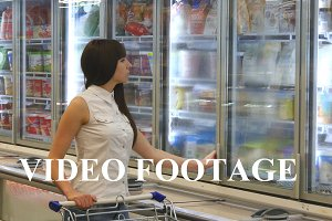 Girl coming up to the fridge in shop