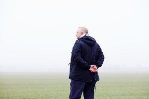 Man in foggy field from behind