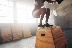 Fit young woman box jumping