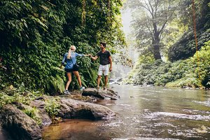 Couple walking by stream in forest