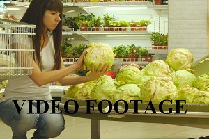 Young woman is choosing cabbage