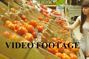 Girl is choosing tomatoes at shop