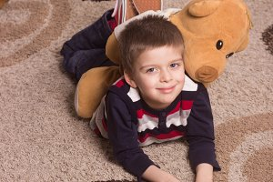 smiling boy laying on floor, carpet.