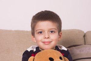 boy sitting holding teddy bear