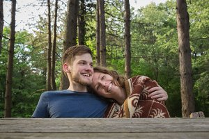 Couple woman man hug forest sitting