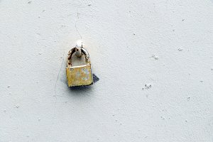 Old padlock on a wall painted white