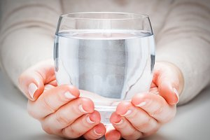 Glass of water in woman's hands.