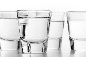 Glasses of vodka on white background