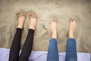 Closeup two feet girls women in sand