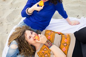 two women eating happy smiling
