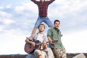three young men singer fun jump