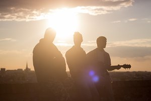 three man music band silhouette sun