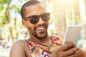 Attractive handsome African radio DJ with sly face expression typing message to his girlfriend with joke or tease using smart phone, smiling while enjoying sunny weather, sitting on bench in park