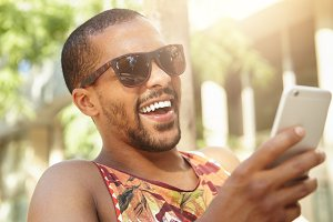 Fashion lifestyle concept. Close up portrait of happy cheerful attractive laughing black man in stylish sunglasses having fun sitting in park, reading ridiculous stories while surfing Internet