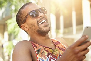 Human emotions and feelings. Cute charismatic dark-skinned man holding smart phone, laughing out loud after receiving hilarious picture from best friend, against background of summer city landscape