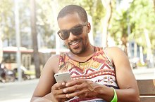 Handsome dark-skinned guy in stylish sunglasses with sly smile flirting online with his girlfriend using web-enabled mobile phone, sitting on bench in city park on hot summer morning, dressed casually