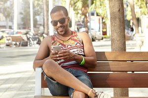 Stylish tourist relaxing in park, sitting in shades of trees with his gadget. African man surfing Internet on his mobile phone, chatting with girls, smiling, watching funny videos on social network