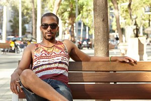 People and lifestyle concept. Black bearded guy in colorful tank top and denim shorts sitting on bench under a tree in city park on sunny day with serious look, waiting for his friends to come