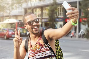 Portrait of happy dark-skinned young man in sunglasses and tank top smiling while taking selfie posing with peace gesture, standing against blurred urban background, using camera of his mobile phone