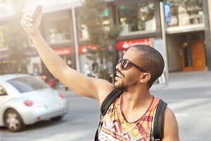 Stylish dark-skinned college student with backpack on his shoulders taking selfie using mobile phone posing and smiling, standing in middle of street on his way to university. Modern lifestyle concept