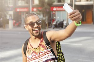 Fashionable young hipster man wearing trendy shades and tank top, having fun, taking self-portrait with smart phone outdoors, walking down street alone on sunny summer day. People and technology