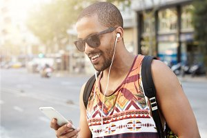 Street fashion. Smiling handsome dark-skinned hipster guy listening to audiobook using his headphones and mobile phone, messaging via social networks, using wireless Internet connection during walk