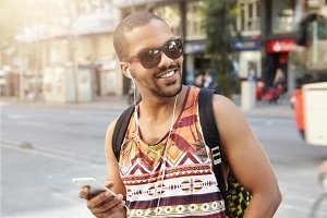 People, technology and communication. Charismatic young African traveler having walk on city street, talking to his friends on mobile phone using handsfree, laughing at jokes, looking happy and glad