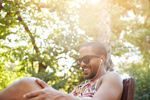 Portrait of attractive dark-skinned man in trendy sunglasses enjoying sunny weather sitting in city park waiting for his girlfriend, smiling while listening to his favourite track using mobile phone