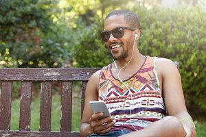 Handsome young African bearded man wearing stylish shades and tank top relaxing in shadow on bench in public park, talking on smart phone with handsfree, smiling, showing his perfect white teeth