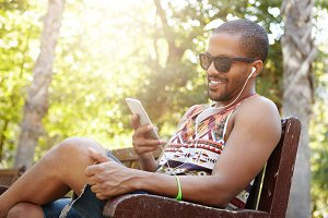 Stylish black male in trendy tank top and denim shorts wearing earphones, sitting on bench under trees, looking happy and cheerful, browsing Internet using electronic device, texting his friends