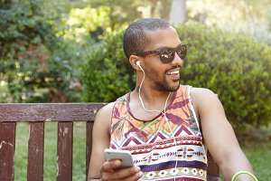 Lifestyle concept. Adult black male in earphones relaxing at park with happy and carefree look, sitting on bench against green trees background, listening to his favorite music using his smart phone