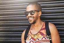 Cropped portrait of smiling handsome African American man wearing sunglasses standing against background of black wall with copy space for your promotional information or advertising concept