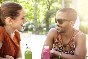 Cute interracial couple drinking smoothie during date. Caucasian girl and handsome African guy in sunglasses having eye contact while talking to each other sitting at street cafe on hot summer evening