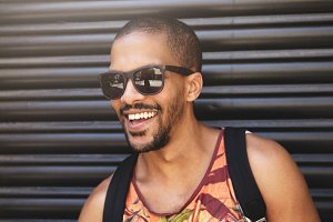 Cropped shot of handsome stylish African man wearing trendy sunglasses and colorful hipster tank top, smiling, showing white teeth, posing against black wall background with backpack on his shoulders