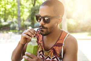 Healthy organic food. Half profile portrait of dark skinned guy drinking tasty fresh green smoothie using straw, sitting in shade on warm summer evening against blurred background of beautiful nature