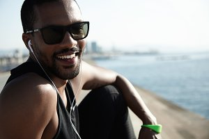 Smiling youngster sitting alone on the seaside and enjoying new album of favorite artist. Urban dark-skinned hipster all in black and stylish sunglasses looking gorgeous on city and sea background.