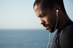 Sideways shot of sad African American man looking down and listening to melancholic music in headphones with serious, pensive face. Young guy sitting alone with blue sky and endless ocean behind him.