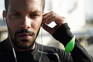 Young black-skinned athlete in black sportive suit putting headphones in ears. Serious man with beard wearing green fitness tracker and looking ahead, thinking about his goals and achievements.