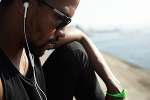 Young African American rapper in black top listening to new tracks outside under blue sky. Handsome and serious man sitting alone on the roadside and chatting with his friends on his digital device.