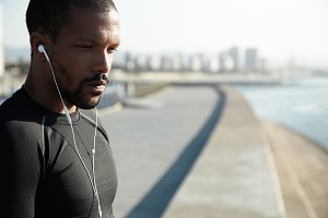 Pensive African American athlete listening to music in white headphones. Thoughtful man brooding upon his purposes and life, sitting on the quay near empty road and far from the city with skyscrapers.
