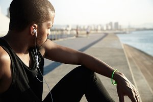 Cropped portrait of young African man with muscular body wearing earphones while resting alone on embankment. Handsome athlete in black tank top listening to music with headphones relaxing outdoors