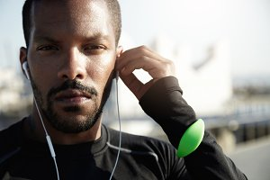 Portrait of purposive fitness trainer preparing himself for tough workout. With serious face, tracker, headphones in ears African American athlete is determined to challenge himself in sport.